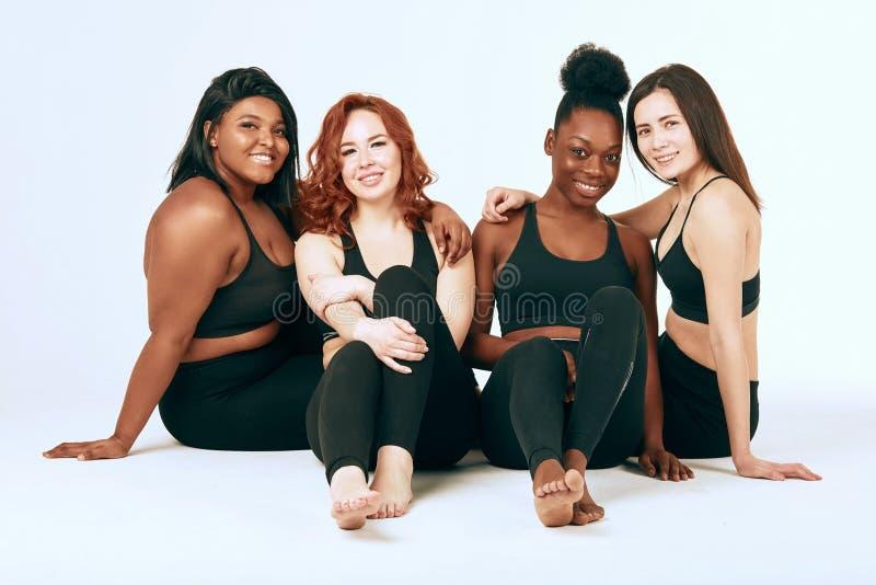 Blandras- kvinnlig med den olika format- och etnicitetst?llningen tillsammans och leende arkivbilder