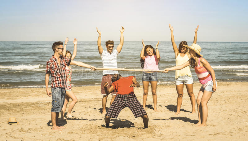 Blandras- lyckliga vänner grupperar att ha gyckel med limbon på stranden arkivfoton