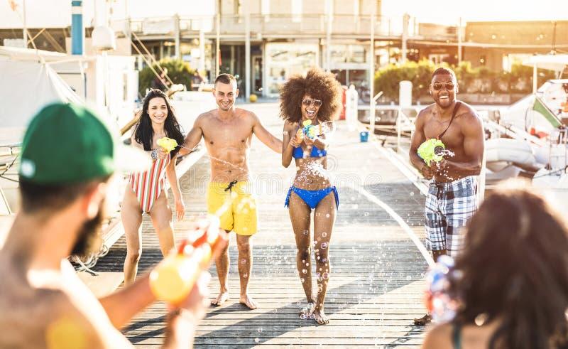 Blandras- lyckliga vänner som har galen gyckel med waterfightstrid på sommarläge - bekymmerslöst semesterbegrepp royaltyfria bilder