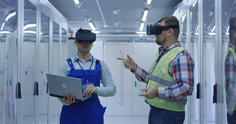 Blandras- män i VR-exponeringsglasarbete på elektrisk station arkivfoto