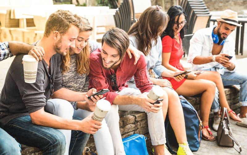 Blandras- millennialsgrupp som använder den smarta telefonen på stadshögskolan royaltyfria foton