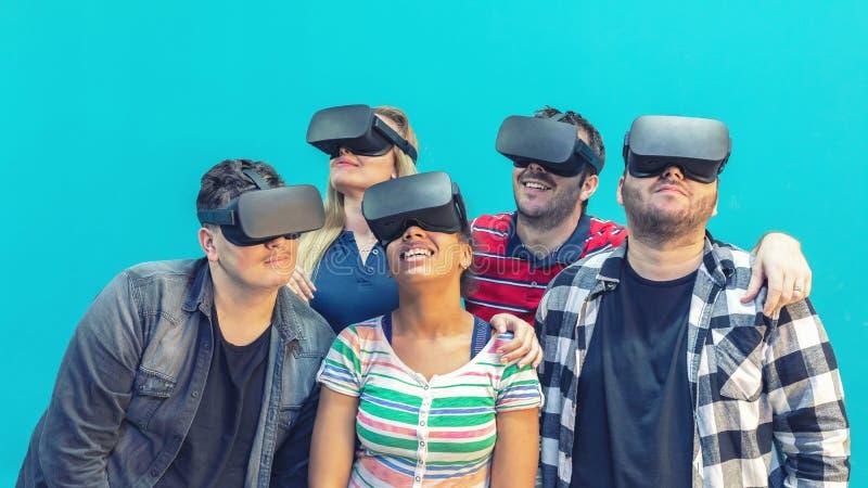 Blandras- olik grupp av vänner som spelar på inomhus vrexponeringsglas - virtuell verklighetbegrepp med ungdomarsom har gyckel ti royaltyfria bilder