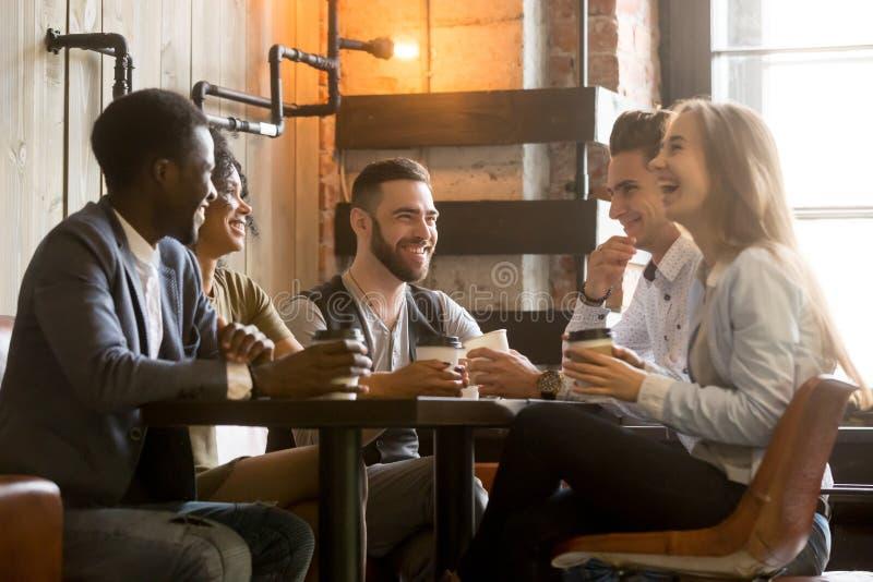 Blandras- unga vänner som har gyckel som skrattar dricka kaffe in royaltyfria foton