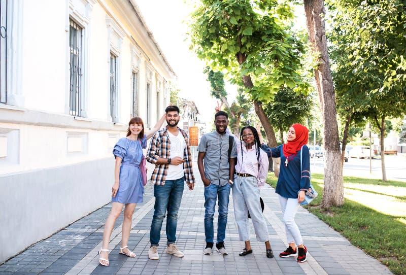 Blandras- unga vänner som poserar på gatan och har gyckel royaltyfria bilder