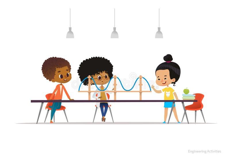 Blandras- ungar som står och sitter runt om tabellen med modellen för upphängningbro på den Begrepp av teknikaktiviteter royaltyfri illustrationer