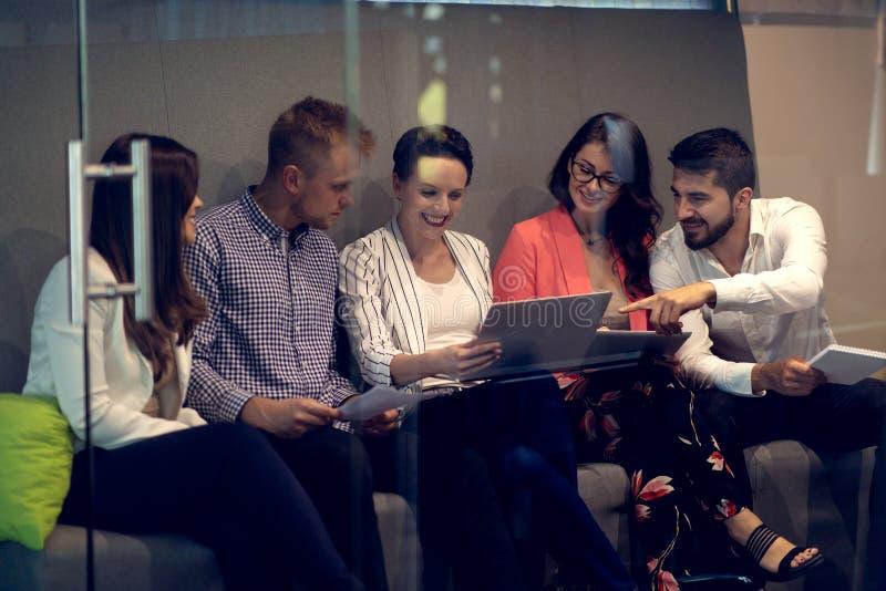 Blandras- ungt id?rikt folk i modernt kontor Gruppen av ungt aff?rsfolk arbetar samman med b?rbara datorn royaltyfria bilder