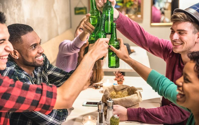 Blandras- vänner grupperar att dricka och att rosta öl på restaurangen royaltyfri bild