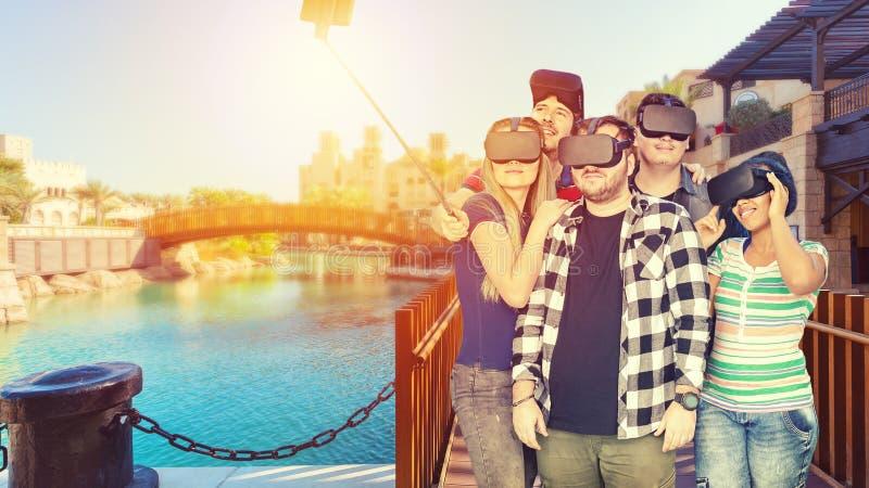 Blandras- vänner med vrexponeringsglas som tar utomhus- selfie - begrepp av virtuell verklighetloppet runt om världen med ungdoma royaltyfria foton
