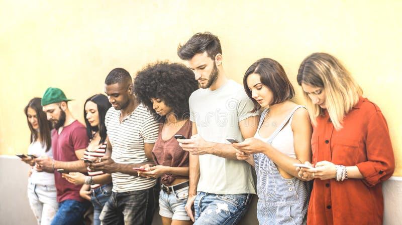 Blandras- vänner som använder den mobila smartphonen på universitetcoampusen - det Millenial folket som missbrukas av smarta tele royaltyfri bild