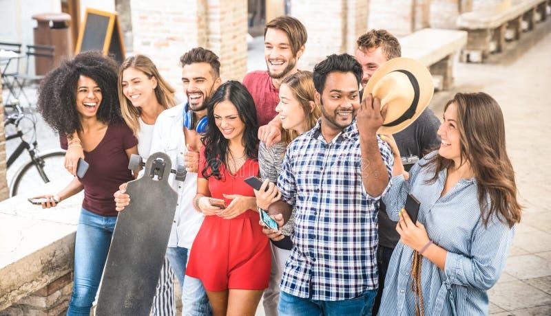 Blandras- vänner som går och talar i centrum - lyckligt G arkivbilder