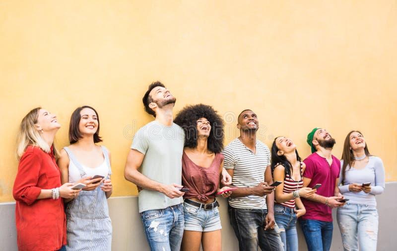 Blandras- vänner som har gyckel genom att använda smartphonen på väggen på avbrottet för universitethögskola - ungdomarsom missbr royaltyfri bild