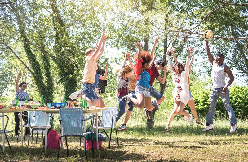Blandras- vänner som hoppar på partiet för trädgård för grillfestpic-nic - mångkulturellt begrepp för kamratskap med ungt lycklig royaltyfri foto