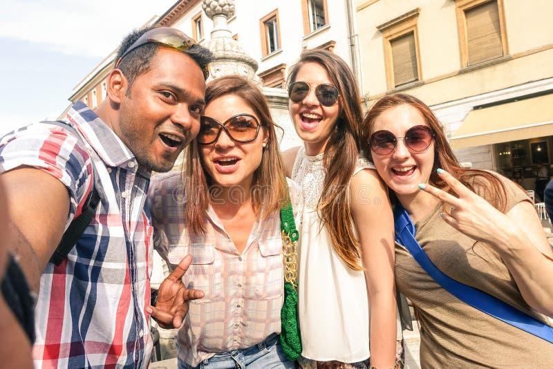Blandras- vänner som tar selfie på staden, turnerar - det lyckliga kamratskapbegreppet med studenten för gen som z har gyckel til royaltyfria bilder