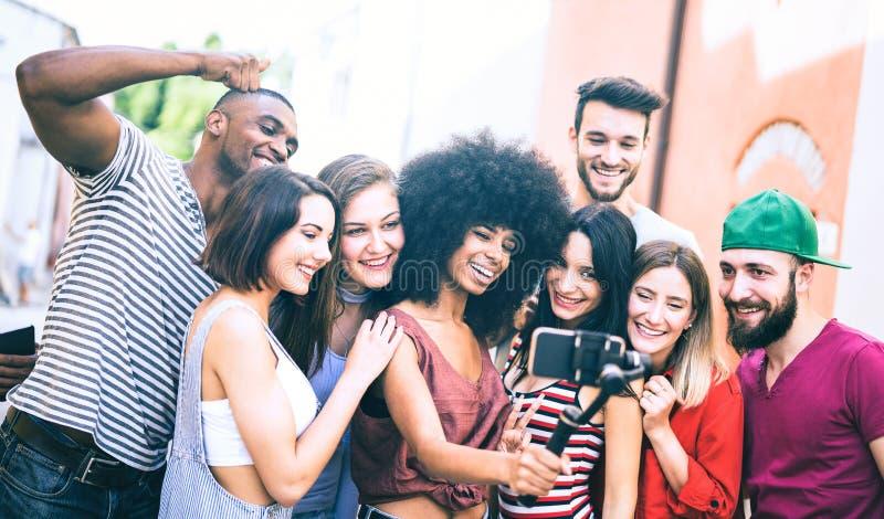 Blandras- vänner som tar video selfie med mobiltelefonen på den stabiliserade gimbalen - ungdomarsom har gyckel på nya techtrende arkivbild