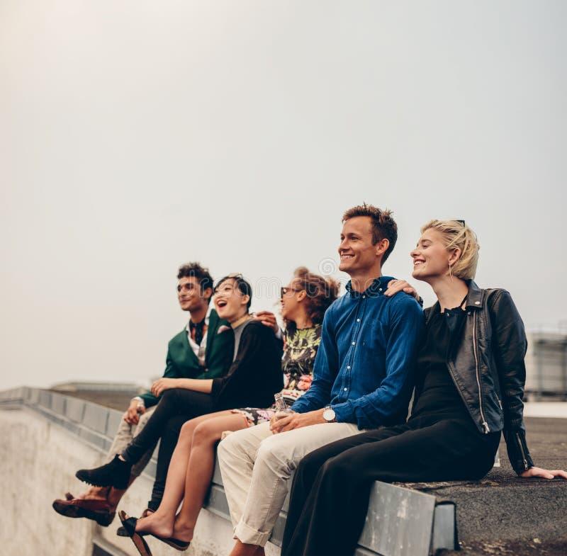 Blandras- vänner som tycker om på terrass arkivfoto