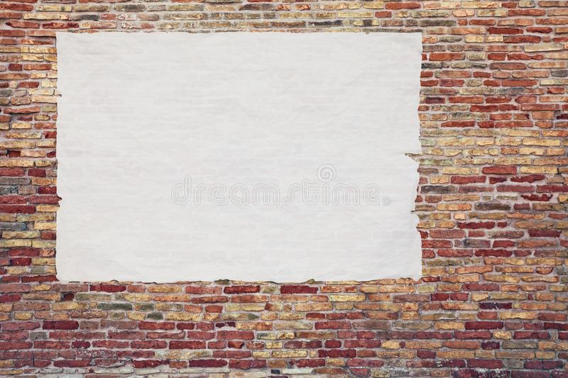 Blank advertising poster glued to the brick wall. Copy space in street billboard stock photo