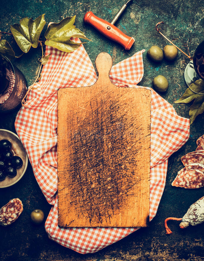 Blank aged cutting board on traditional red plaid napkin , around lying snacks and antipasti: wine,olives,salami and grape leaves royalty free stock images