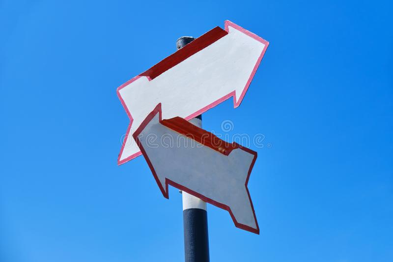 Blank arrow signs with two arrows pointing in different directions, on a bright blue sky stock photos
