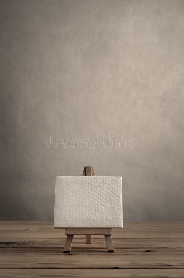 Blank Art Canvas on Wooden Easel against Empty Wall with Planked. Blank art canvas on easel standing on wood plank floor. Empty wall behind provides copy space stock image