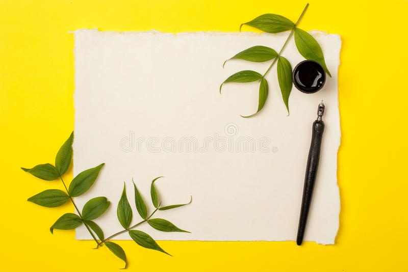 Blank artist sheet on bright yellow background with calligraphy pen and ink. View from the top. Artistic mockup template for your stock photos