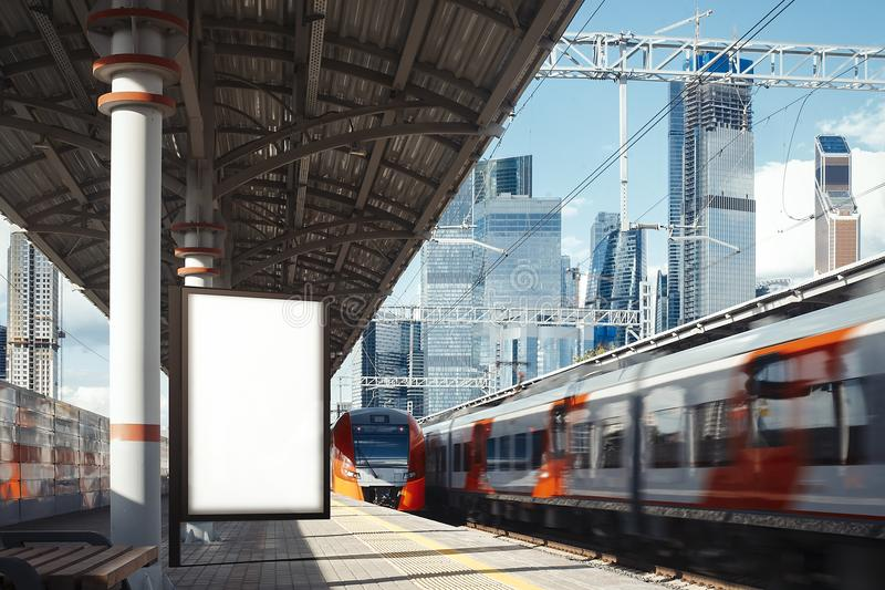 Blank banner at metro platform with arrived train on a background, 3d rendering. Blank white banner at metro station with arrived train and skyscrapers on a royalty free stock photos