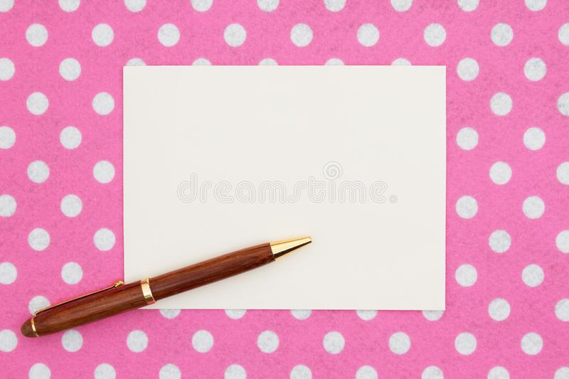 Blank beige greeting card with pen on pink and white polka dot fabric. That you can use as a mock up for your message stock photos