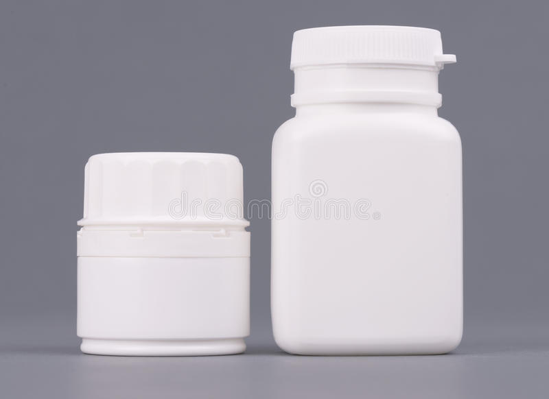 Blank big and medium size medicine white plastic packaging bottles for cosmetics, vitamins, pills or capsules. Packaging stock photo