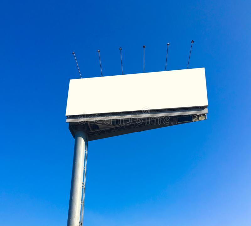 Blank billboard at blue sky background. Mock up of blank white billboard on a background of blue sky. Outdoor triangle billboard or advertising poster with copy stock photo