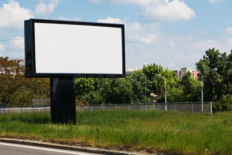 Blank billboard on grass, blue sky background - for new advertisement royalty free stock photography