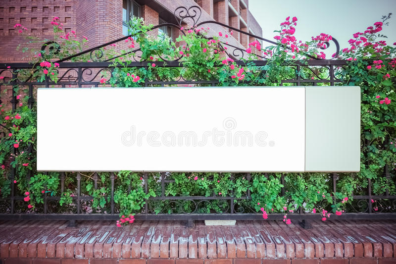 Blank billboard on iron fence stock image