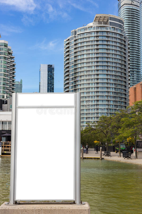 blank billboard near a pond in front of trees and appartment buildings stock photos