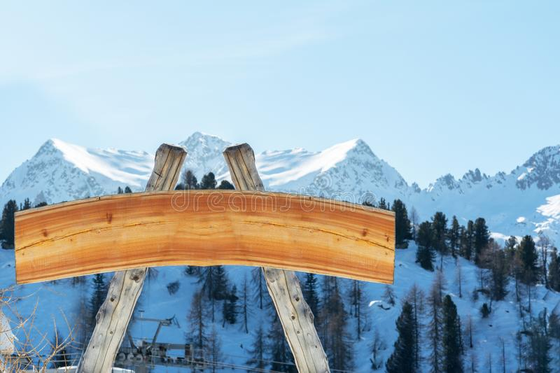 Blank billboard for outdoor advertising from logs and a wooden board on a ski slope against the backdrop of the mountains. The con royalty free stock photos