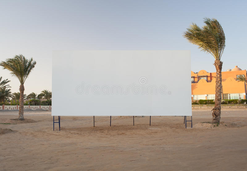 Blank billboard with palm trees stock images