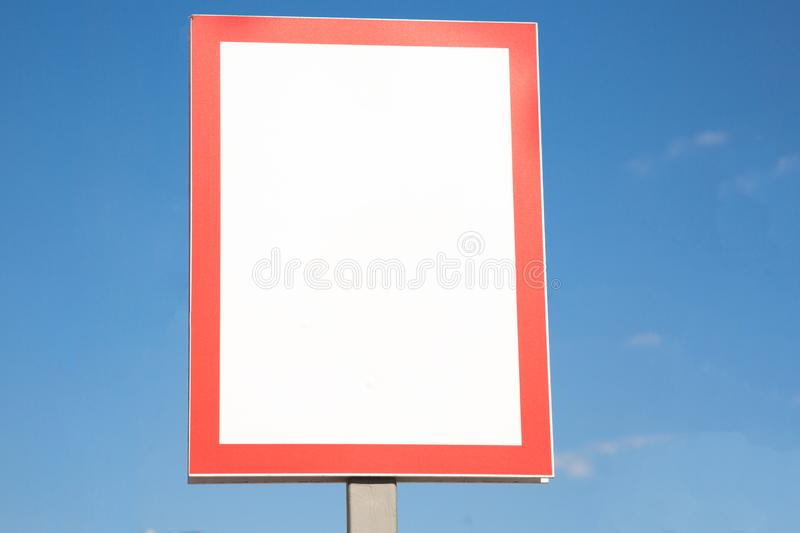 Blank billboard sign in a red frame on a background of blue sky stock image