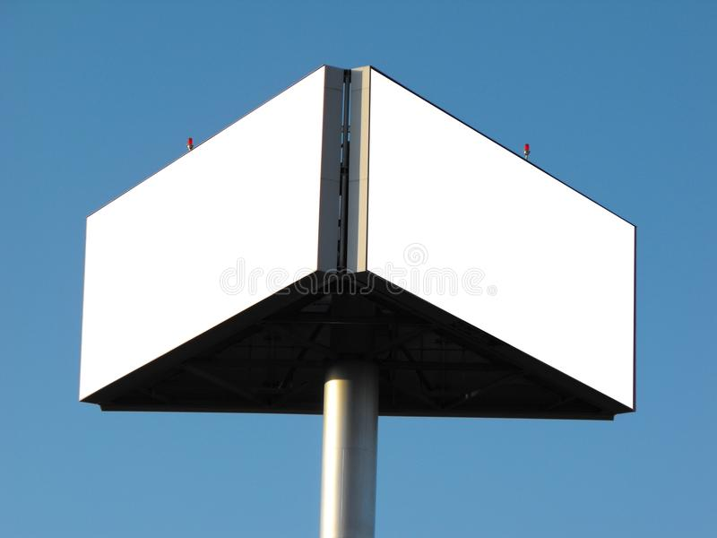Blank billboards. Two blank sides of a triangular billboard on a silver pole, isolated against a cloudless blue sky background stock image