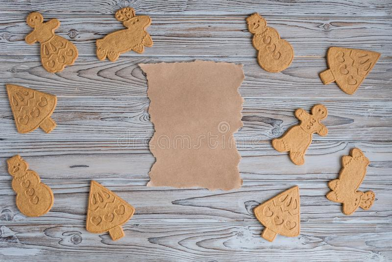 Blank biscuit gingerbread differents cookies ready to decorate. Craft paper, rolling pin in middle wooden grey table. For copy space. Flat lay royalty free stock photos