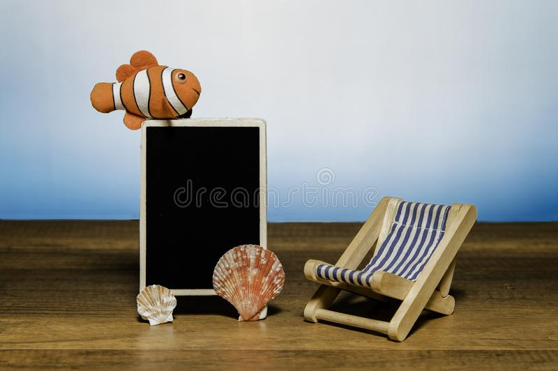 Blank black board with clown fish, sea shell and beach bed stock image