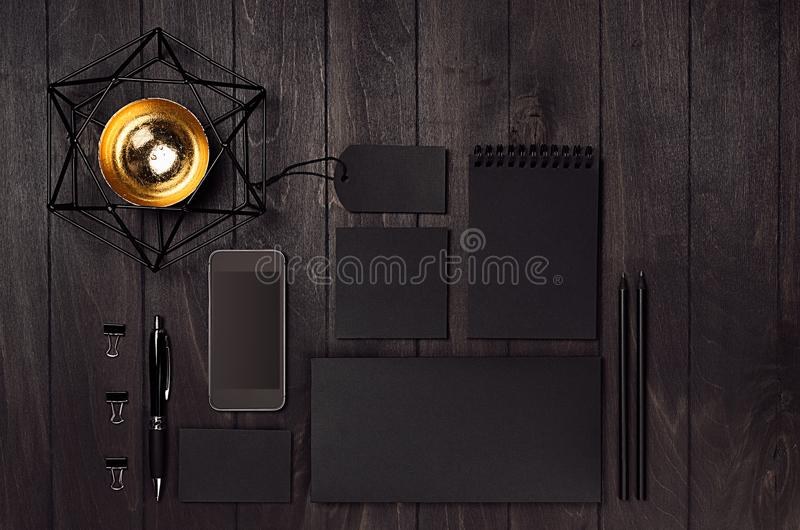 Blank black business stationery set with phone, coffee cup, gold decoration on dark elegant wood table. Modern fashion simple work place royalty free stock photos