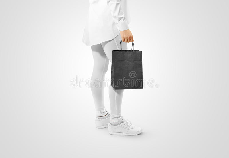 Blank black craft paper bag design mockup holding hand. Clipping path. Woman hold kraft textured purchase pack mock up. Clear shop bagful branding template stock images