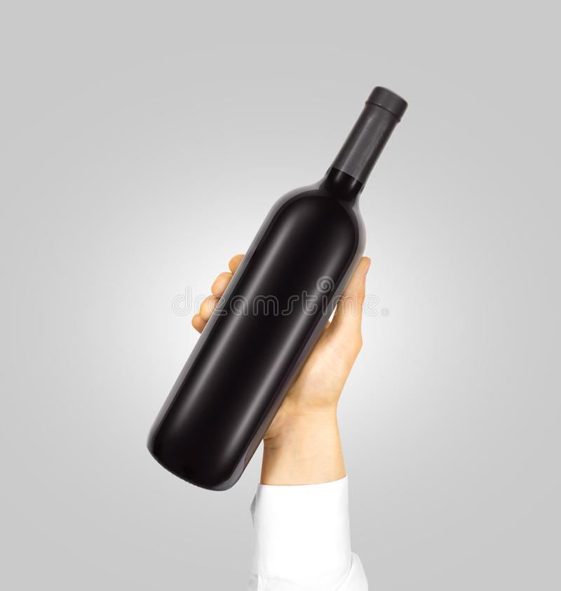Blank black label mockup on bottle of red wine. Blank black label mockup on black bottle of red wine in hand isolated. Alcohol bottle mock up presentation ready royalty free stock image
