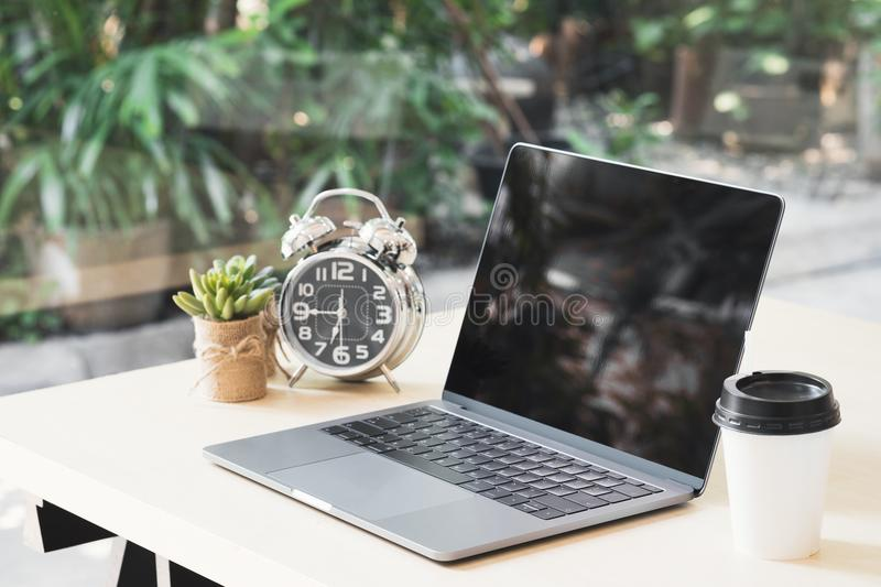 Blank black laptop screen display on wooden table with a cup of. Coffee, clock and small plant pots in office while break time. Mock up computer notebook on stock photography