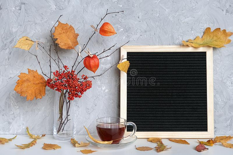 Blank black letter board frame and Autumn bouquet of branches with yellow leaves on clothespins in vase, cup of tea on table. Mockup Template for your text royalty free stock images