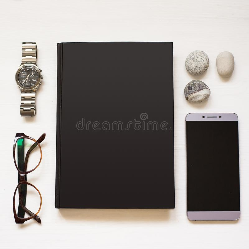 Blank black notebook isolated on white textured wood background with business man`s things. Flat Lay book. Top View. Copy space stock images