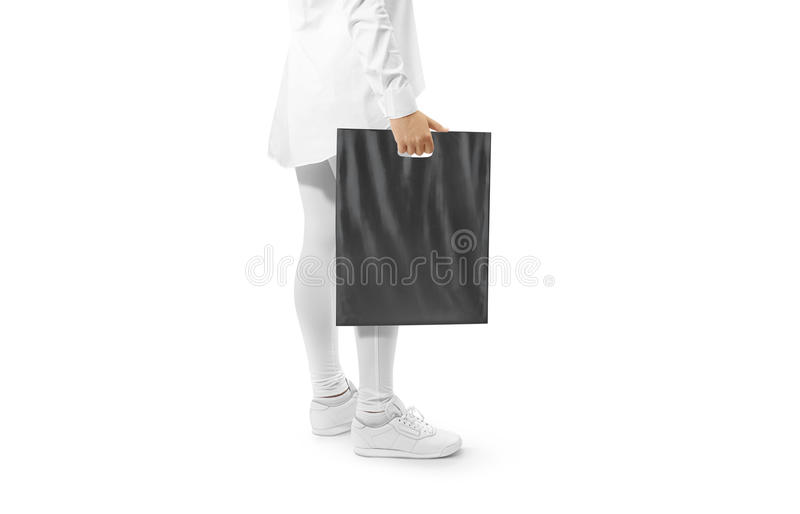 Blank black plastic bag mockup holding hand. Woman hold dark carrier sac mock up. Grey bagful branding template. Shopping carry package in persons arm stock images