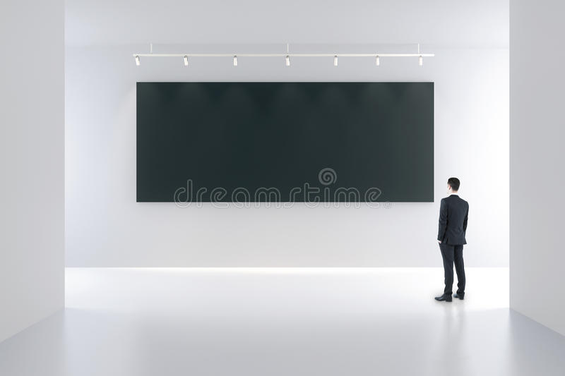 Blank black poster and businessman in white empty room stock photos