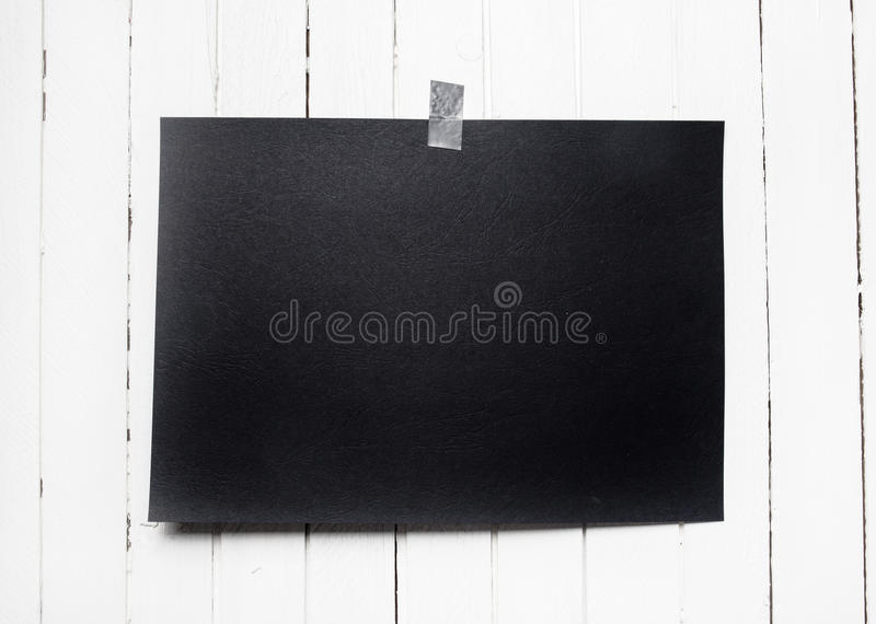 Blank black poster hanging on a tape on white wooden plank wall. Template background for your design stock photo