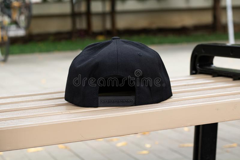 Blank black snapback hat cap flat visor with black color. Blank snapback hat cap flat visor with black color in outdoor, ready for your mock up design or royalty free stock photo