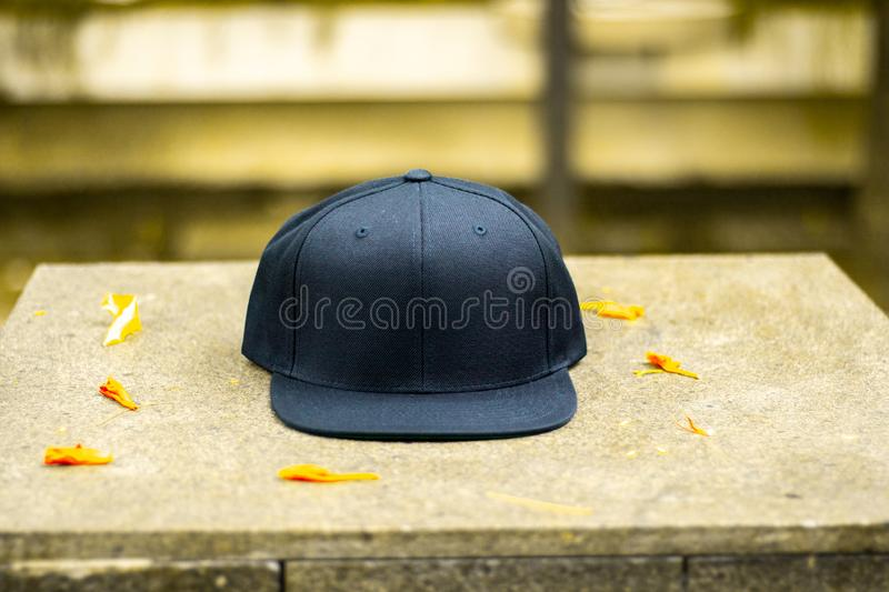 Blank black snapback hat cap flat visor with black color. Blank snapback hat cap flat visor with black color in outdoor, ready for your mock up design or royalty free stock photography