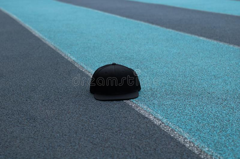 Blank black snapback hat cap flat visor with black color. Blank snapback hat cap flat visor with black color in outdoor, ready for your mock up design or stock photo