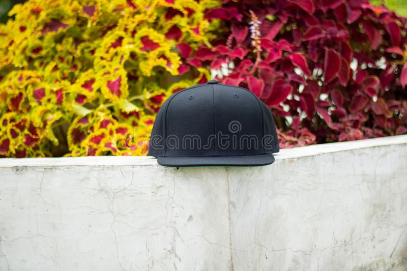 Blank black snapback hat cap flat visor with black color. Blank snapback hat cap flat visor with black color in outdoor, ready for your mock up design or stock photography